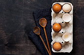 Raw chicken eggs in box with napkin and wooden spoons on an old wooden background. Ingredients for making an omelet. Top view. Mock up.