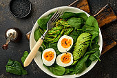 Fresh vegetable salad with avocado, asparagus, crumpled eggs with black sesame seeds and spinach on plate on light slate, stone or concrete background. Balanced lunch in bowl. Top view. Mock up.