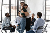 Couple of therapy group mates hugging each other on meeting