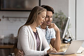 Happy couple relax at home using laptop
