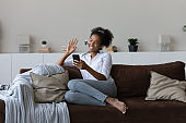 Happy millennial african woman holding web camera mobile video call.