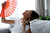 Close up overheated woman waving paper fan, breathing air