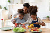 Patient african mom teaching son and daughter to prepare salad