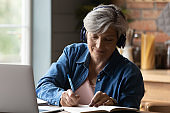 Elderly woman in headphones watch webinar on laptop take notes