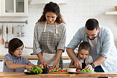Happy family with two little kids cooking salad, cutting vegetables
