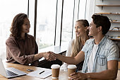 Excited couple clients close deal with realtor