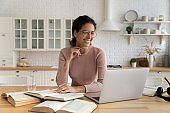 Latin lady reading book on laptop distracted from paper literature