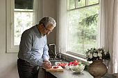 Mature adult man cooking dinner at home
