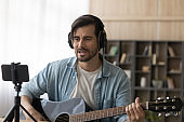 Millennial male artist play guitar recording video