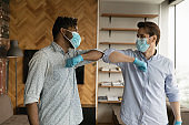Diverse men touch elbows greeting during coronavirus pandemics