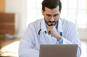 Concentrated young male gp doctor working on computer.