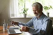 Happy senior customer shopping online from home
