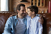 Smiling young dad and little son relax at home