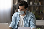 Young businessman in facial mask working on computer in office.