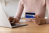 Young woman pay for goods at web store using card