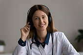Head shot portrait of happy skilled young doctor in headset.