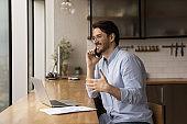 Smiling man work on laptop talking on smartphone