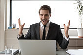 Overjoyed businessman triumph reading news on laptop