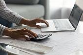 Close up woman using laptop and calculator, calculating bills