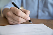 Close up male hand holding pen signing insurance agreement
