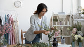 Concentrated millennial woman floral decor specialist preparing arrangement from flowers