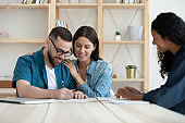 Happy couple sign document closing deal at meeting