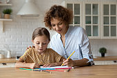 Caring millennial nanny help child to draw picture in album