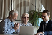 Male realtor consult senior couple buyers in office