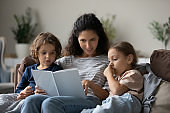 Caring Latin mom and two kids read book at home