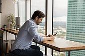Caucasian man sit at desk using smartphone