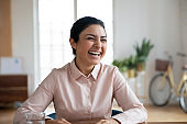 Overjoyed Indian woman have fun talking at workplace