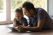 Little daughter and loving father reading book on tablet indoors