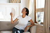 Overheated biracial woman use hand fan at home
