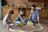 Loving young dad and two kids constructing railroad of bricks