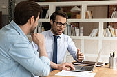 Male colleagues brainstorm working on computer in office