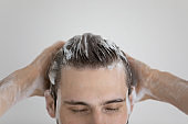 Face of relaxed attractive guy with closed eyes washing head