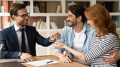 Happy millennial couple receiving keys from realtor, purchasing real estate