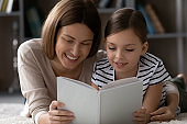 Happy bonding young mother and little daughter reading book.