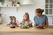 Happy young mother with two little kids preparing lunch