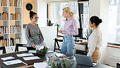 Three confident diverse businesswomen brainstorming project, standing in office