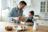 Smiling father and adorable little daughter cooking dough in kitchen