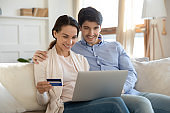 Close up happy couple paying by credit card online together