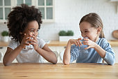 Cute smiling diverse little girls drinking fresh water in kitchen