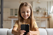 Smiling small girl talk on video call on cell