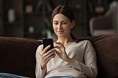 Close up satisfied young woman using smartphone, sitting on couch