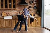 Young couple having date indoors dancing passionate disco at kitchen