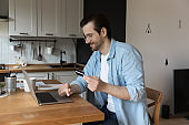 Happy man shopping online on laptop with credit card