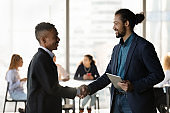 Smiling ethnic businessmen handshake closing deal in office
