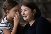 Teen granddaughter and mature grandmother gossip at home