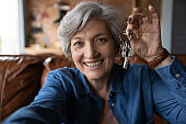 Happy mature woman showing keys from new house